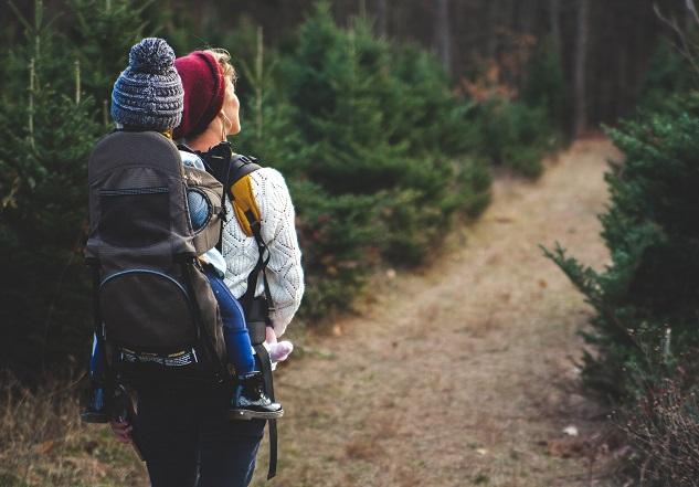 Mulher fazendo trilha com uma criança nas costas por um caminho verde no meio da natureza mostrando como ser uma boa mãe sendo você mesma