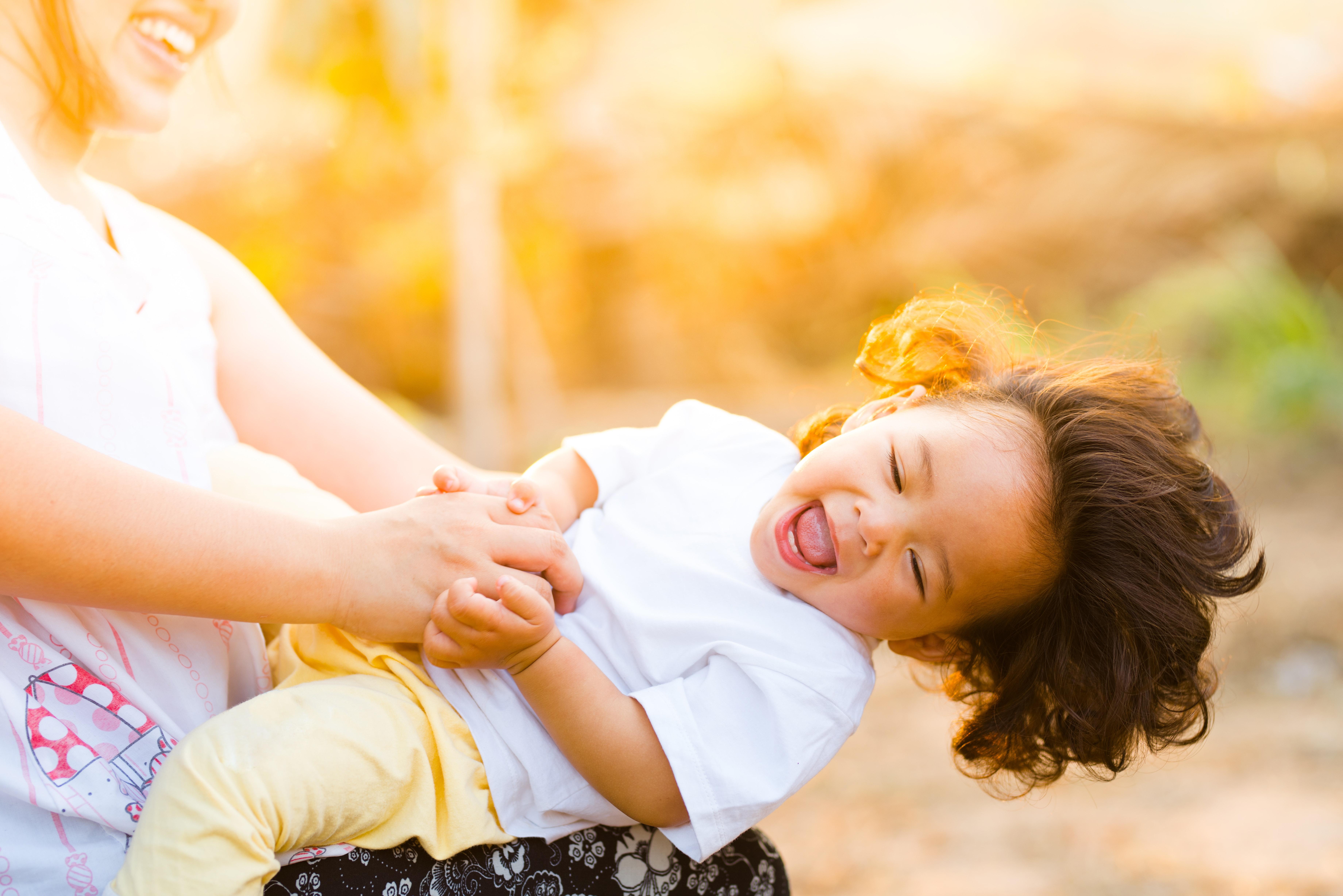 criança brincando de gangorra com uma mulher no por do sol