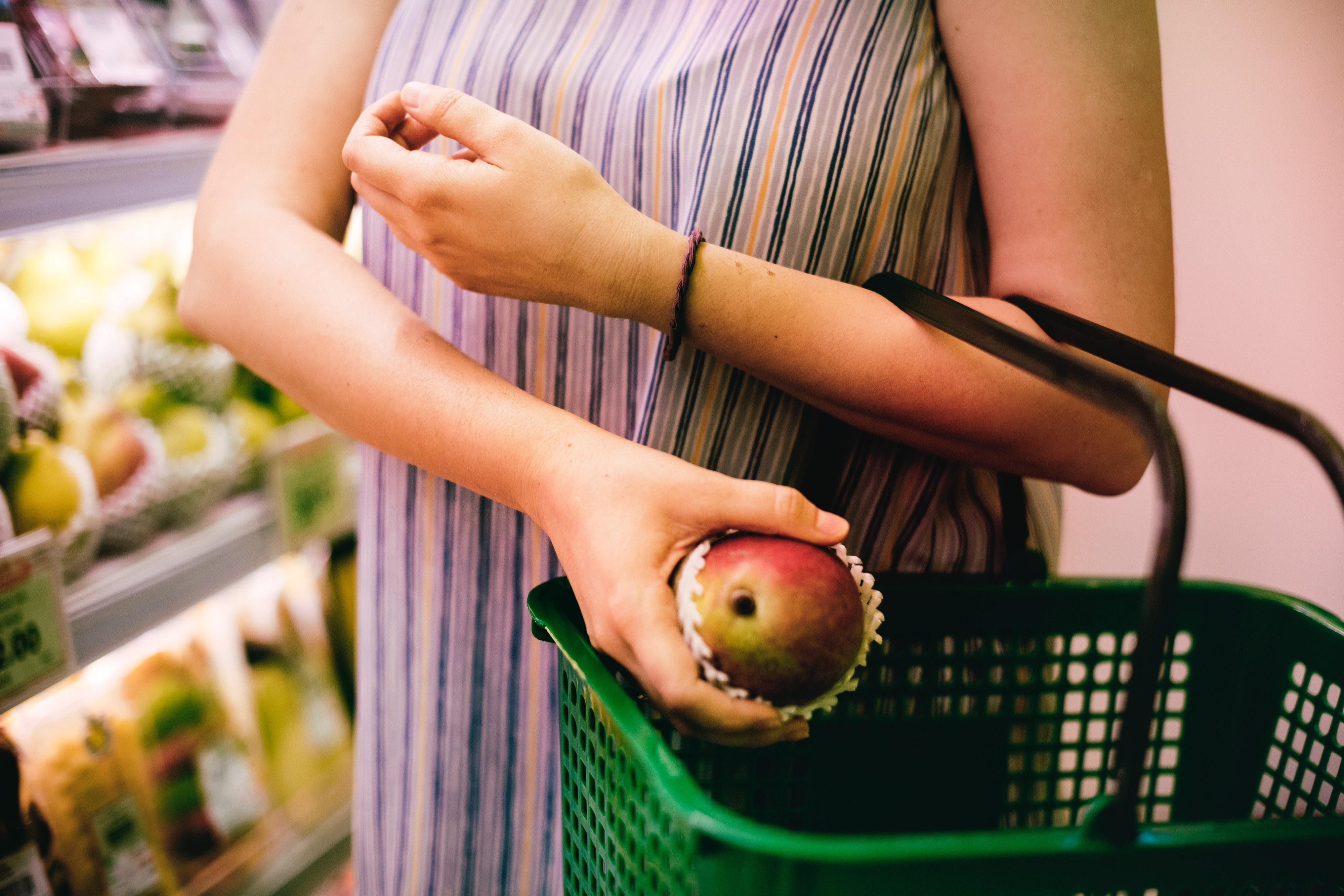 meio corpo de mulher colocando uma maça em uma cesta de mercado mostrando como economizar dinheiro com alimentos