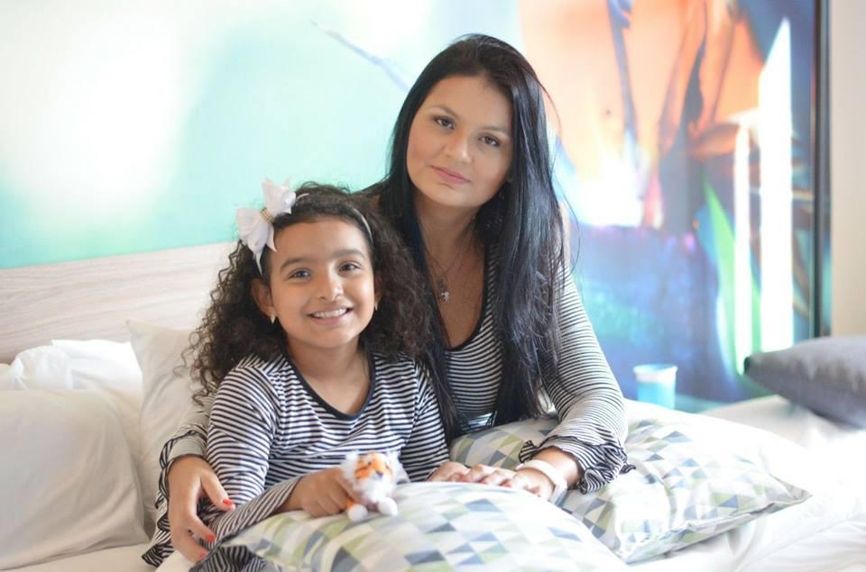 mulher e menina criança sentadas na cama