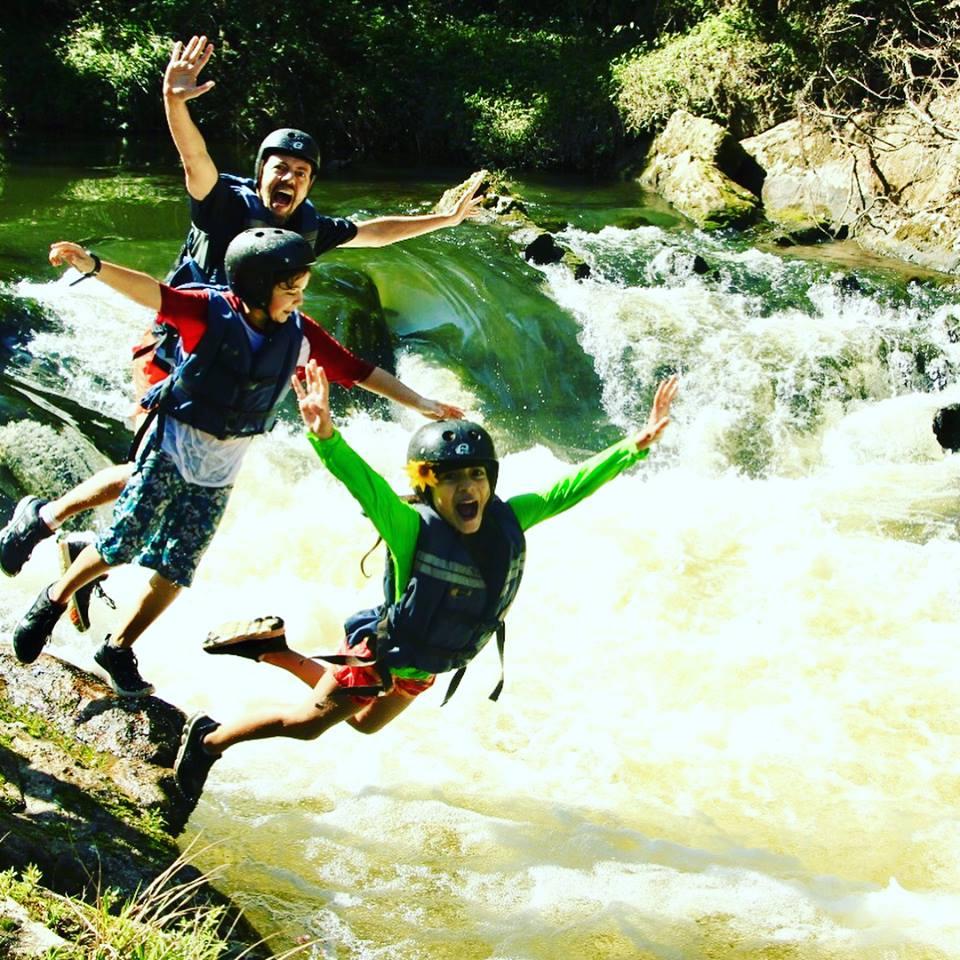duas crianças e um homem pulando no rio com cara de diversão