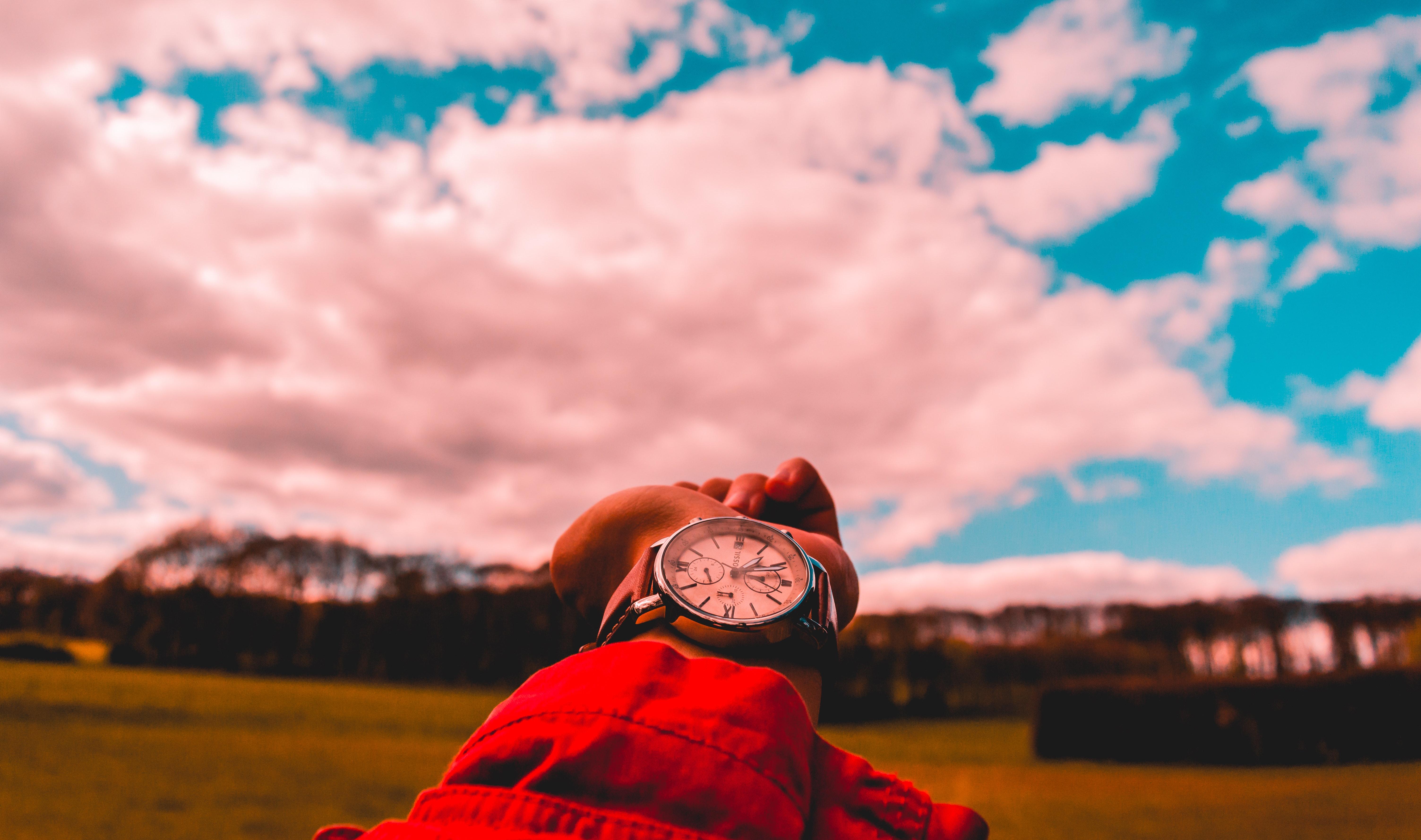 braço com relógio apontando o cel
