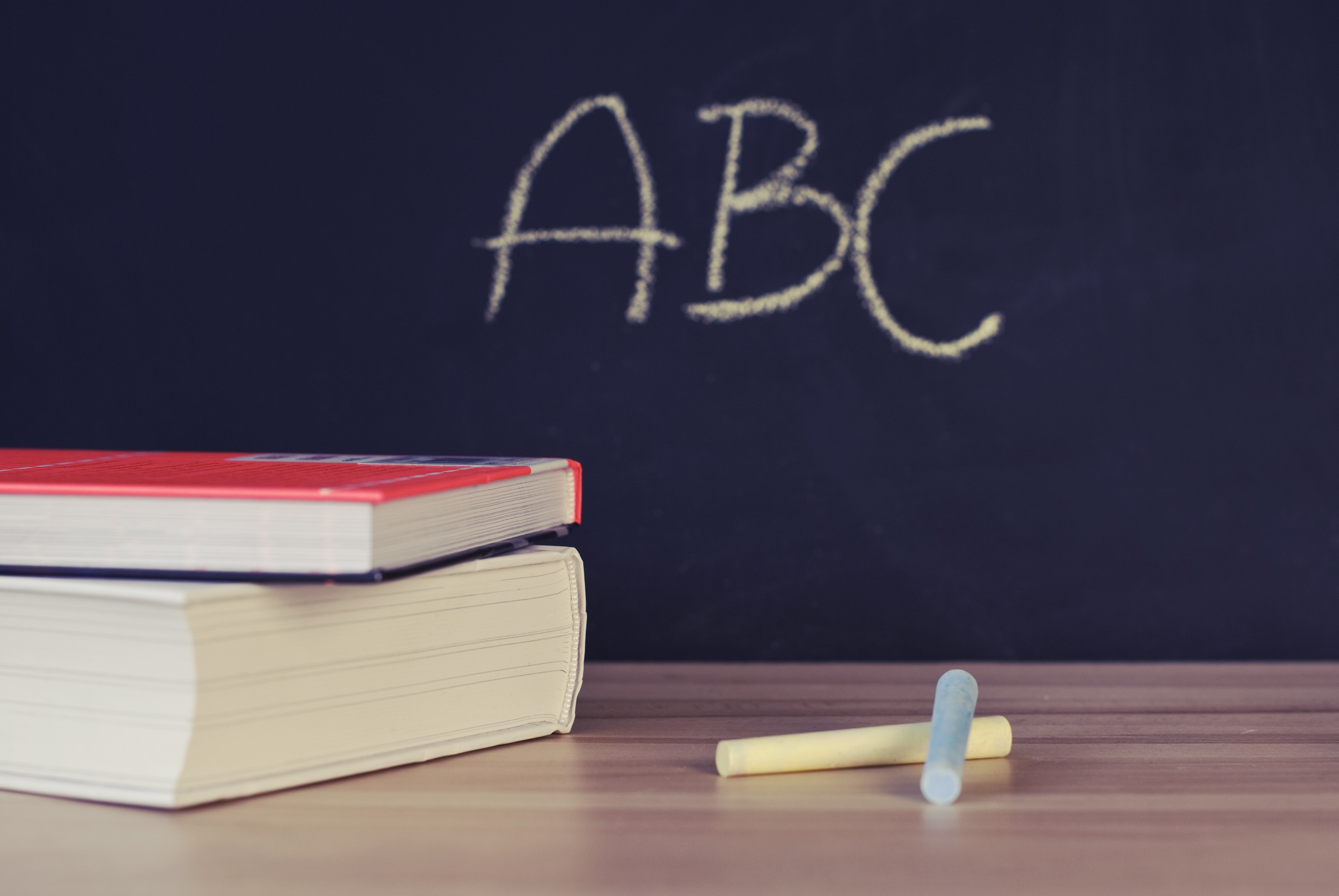 dois livros em cima de uma mesa com um giz e no fundo escrito ABC