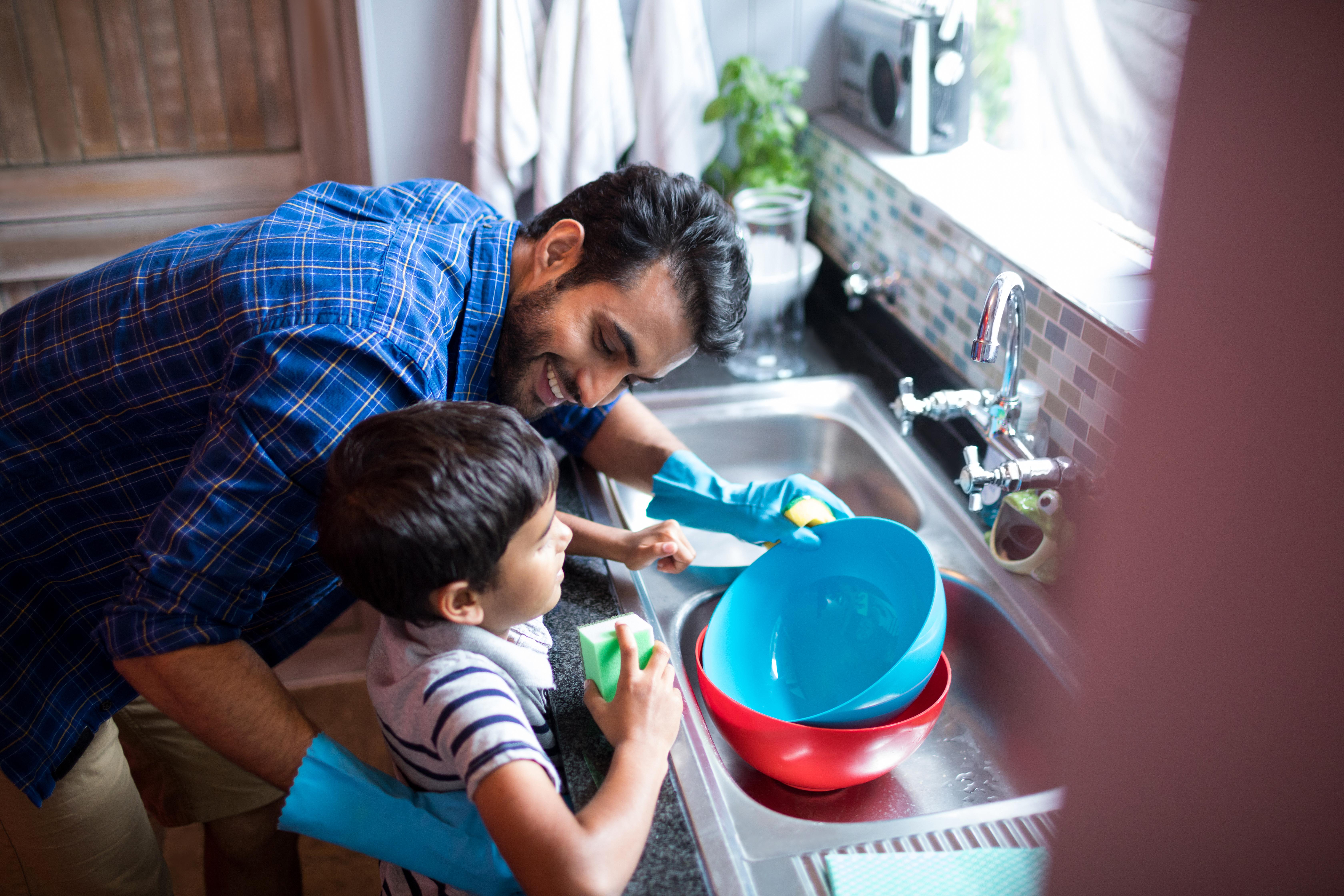 homem e criança lavando louça em uma pia