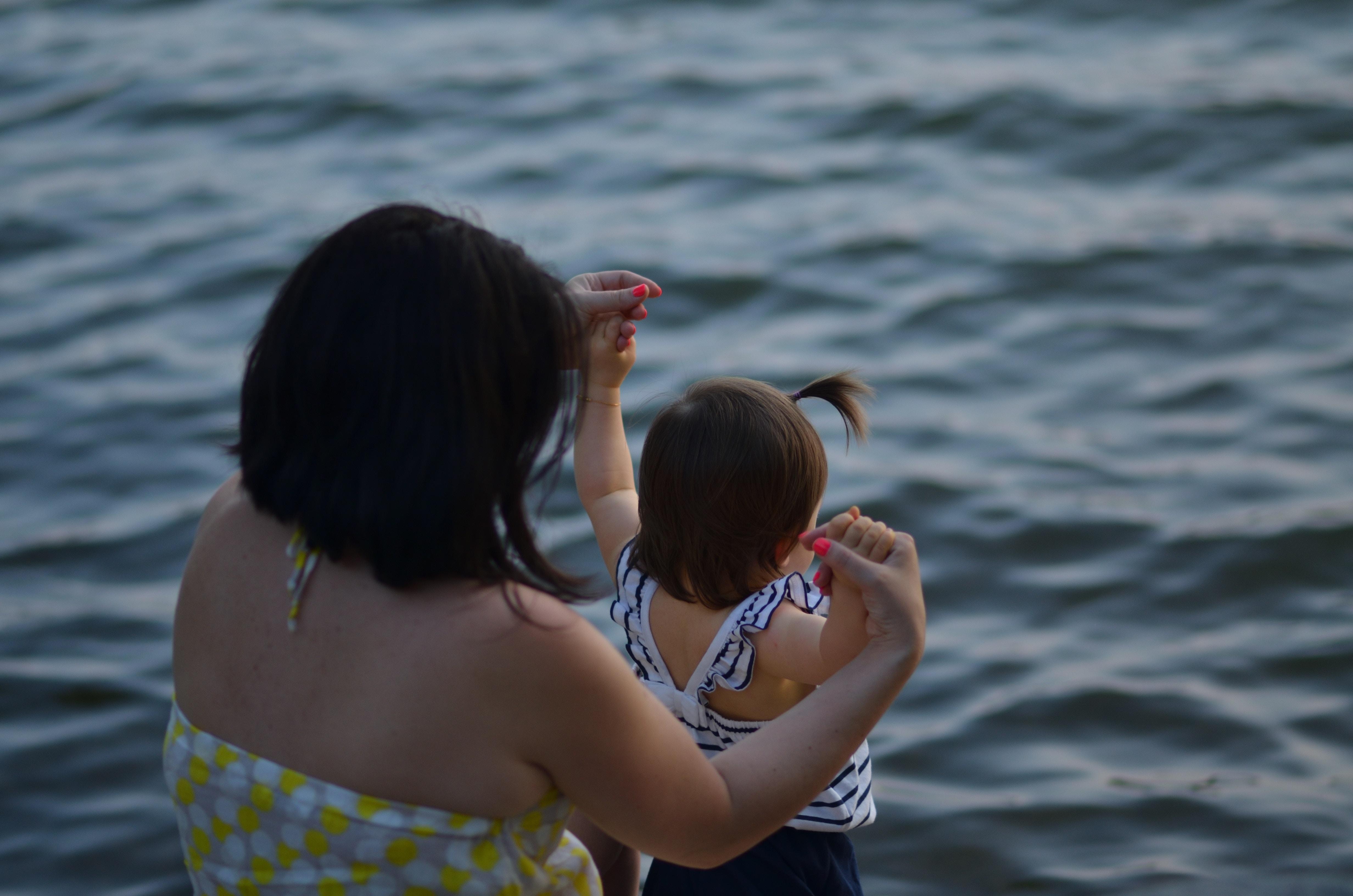 mulher segurando a mão de uma bebê na beira da água