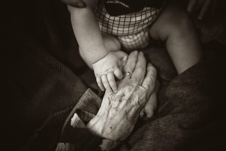 mão de uma pessoa velha junto com mão de um bebê