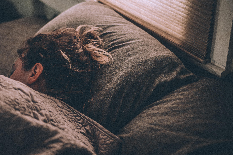 cabeça de uma mulher deitada em uma cama