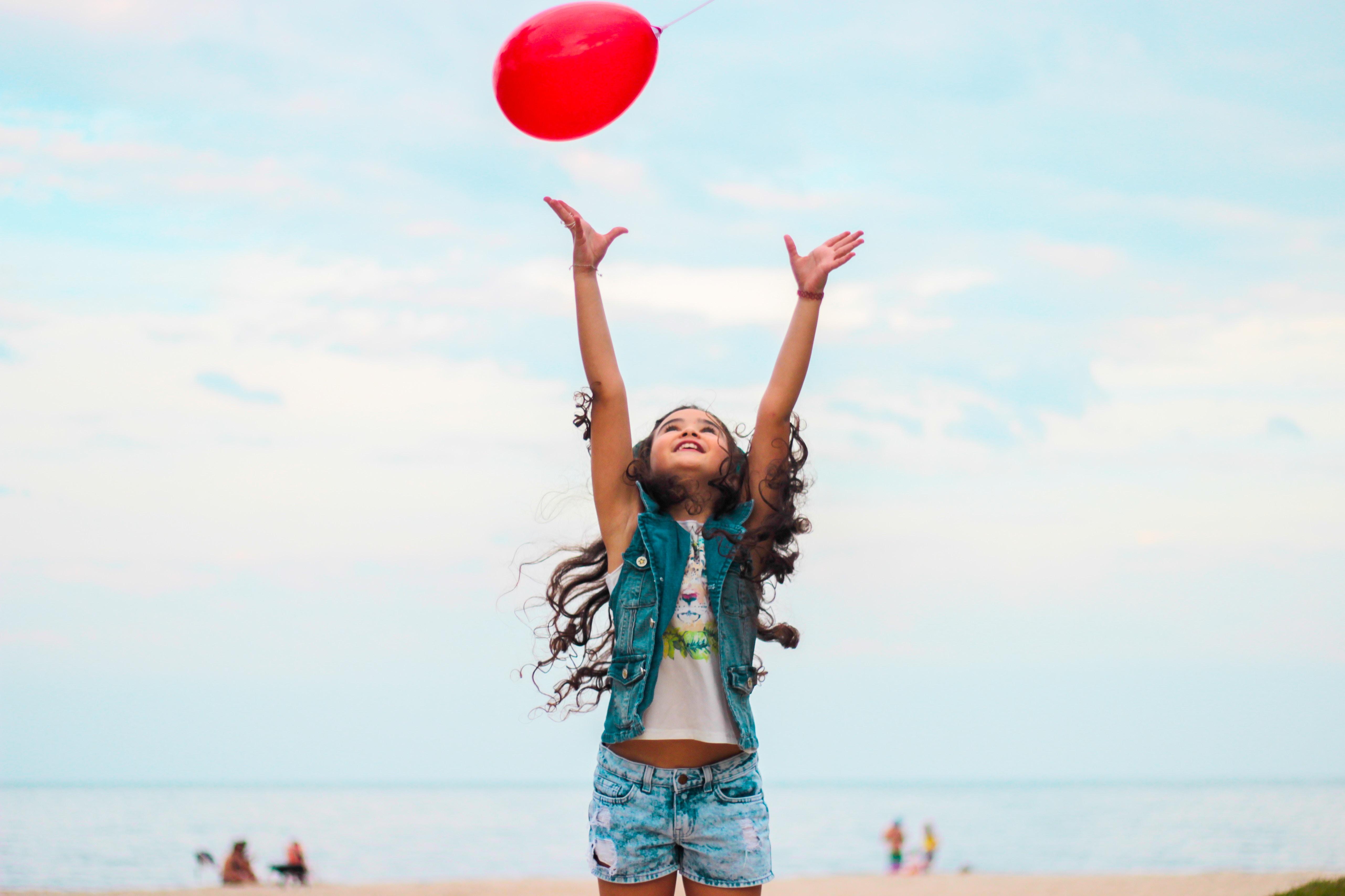 menina criança jogando balão vermelho para cima