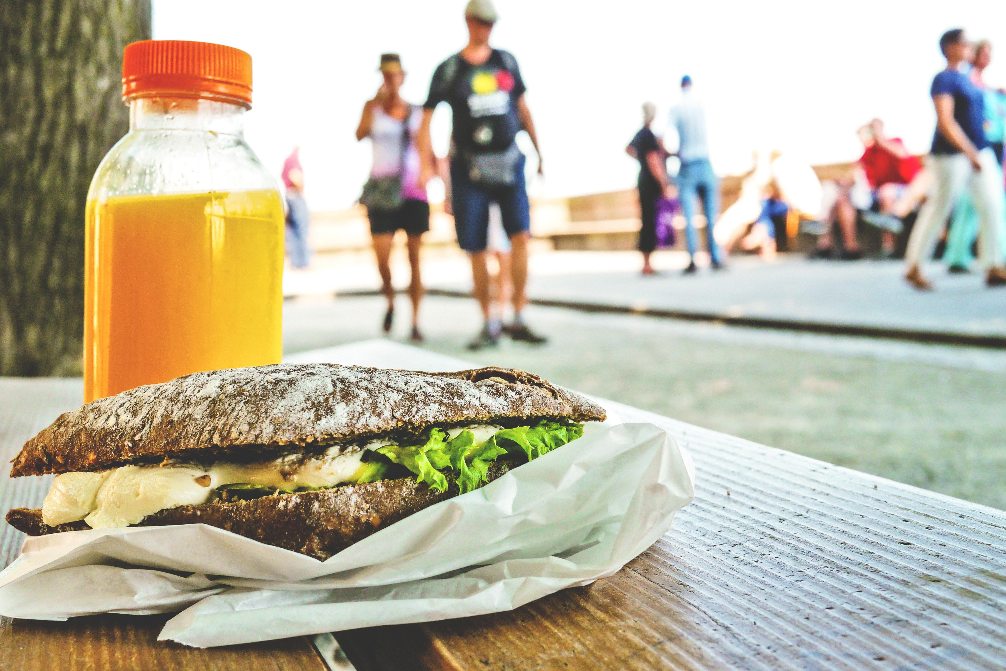 sandwich e suco em cima de um banco, na rua, com pesoas passando atras