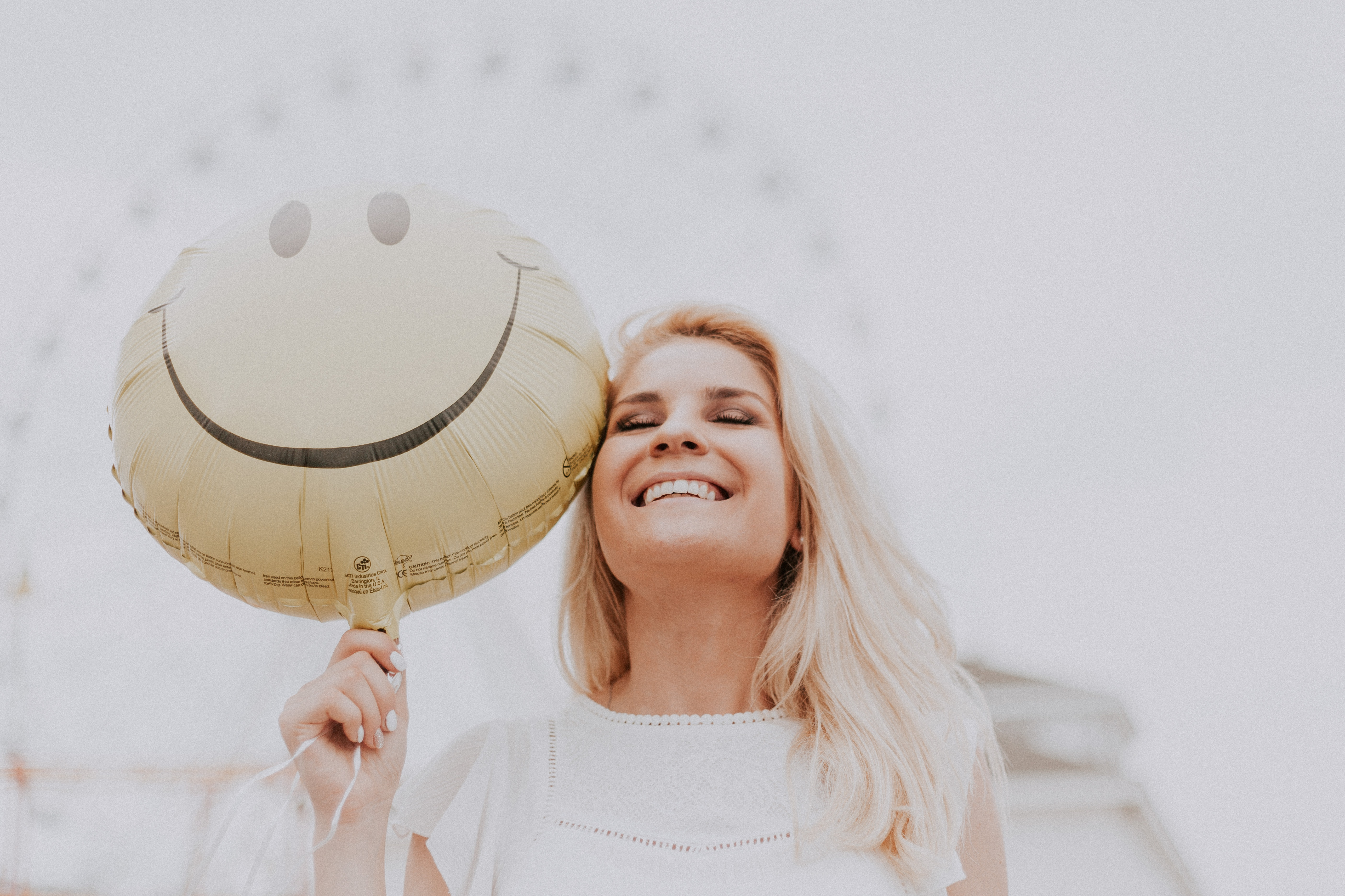 mulher loira segurando balão com um smile sorrindo