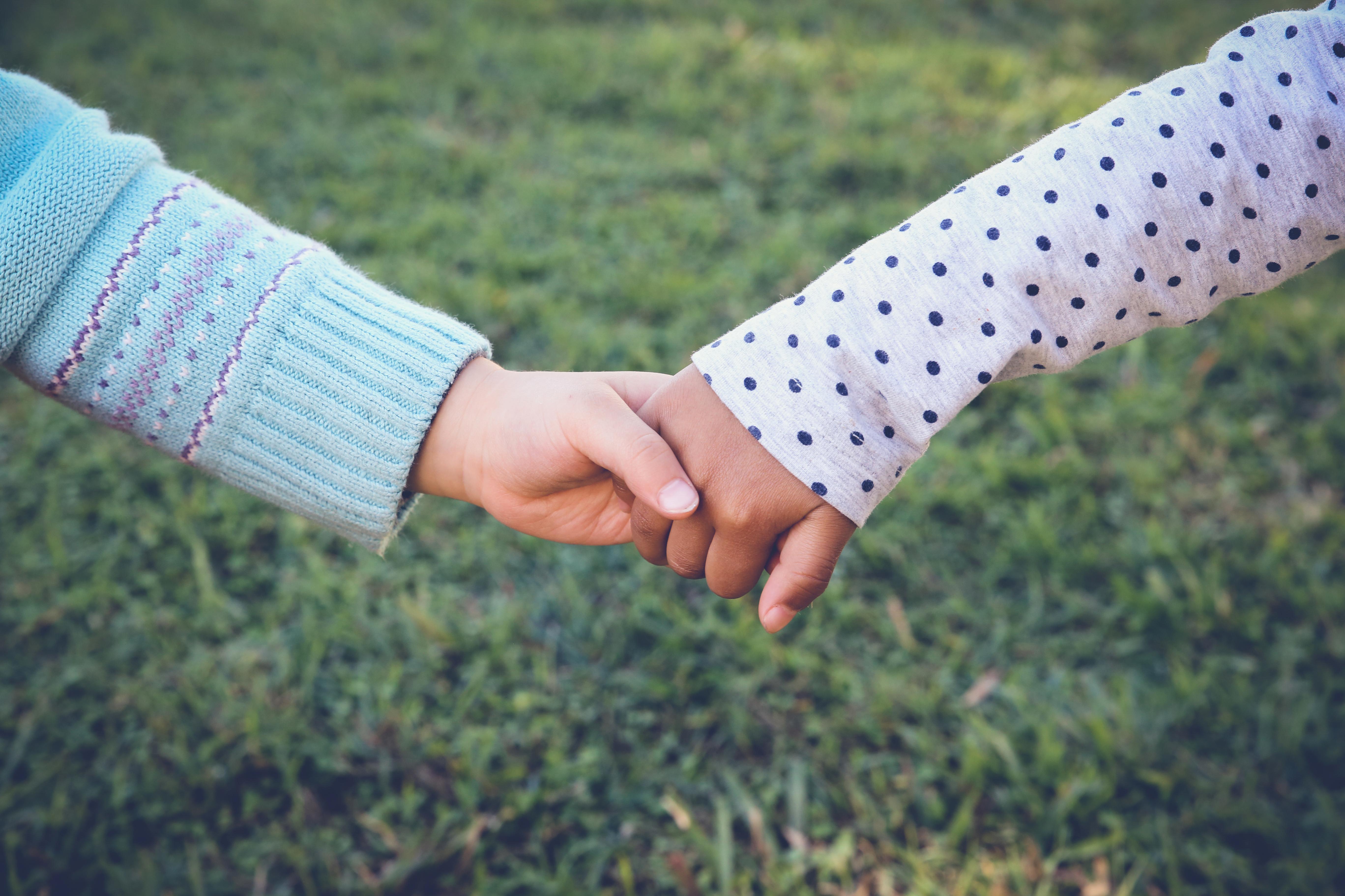 A mão de uma criança branca dando a mão para uma criança negra