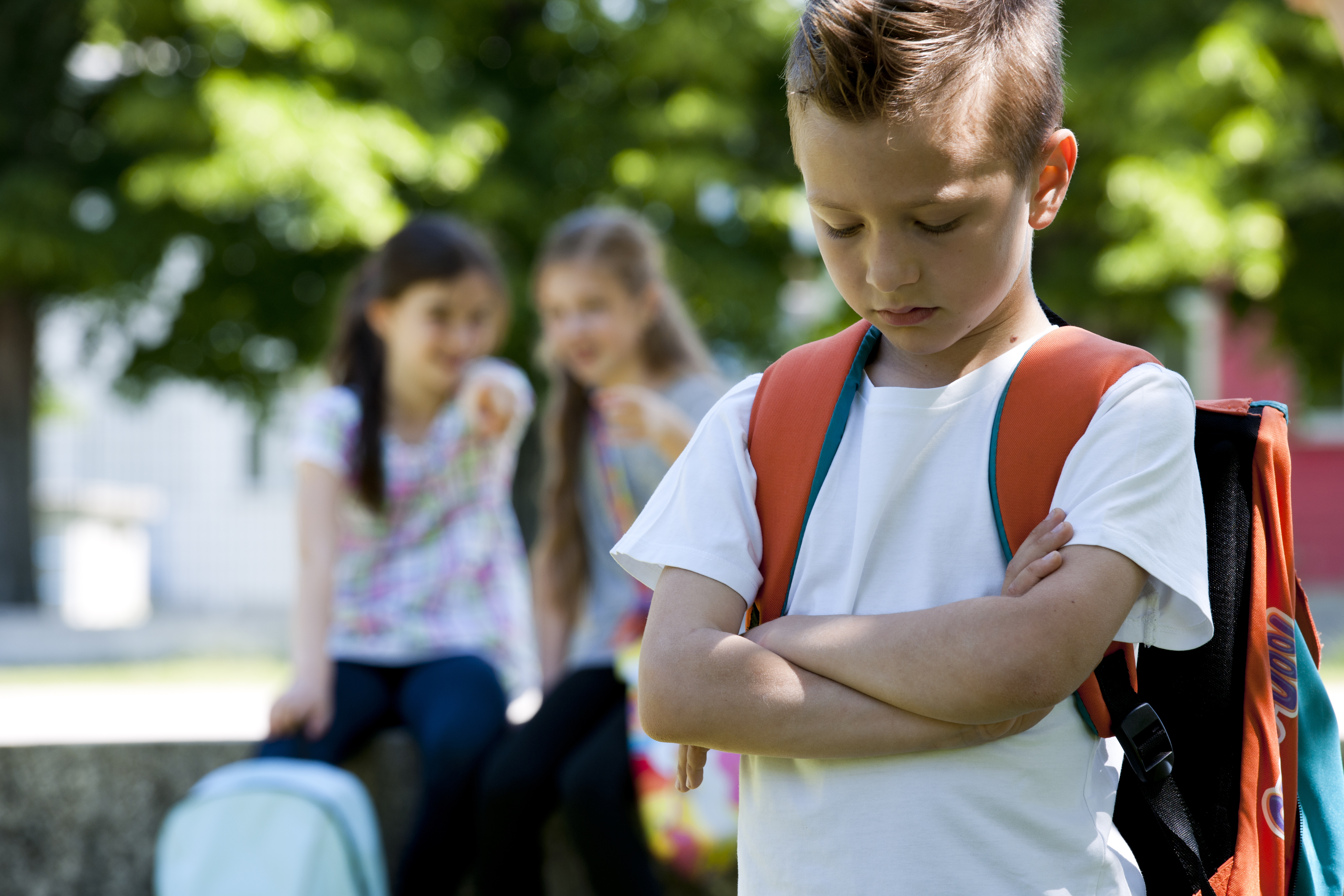 menino triste com duas meninas atrás zombando dele