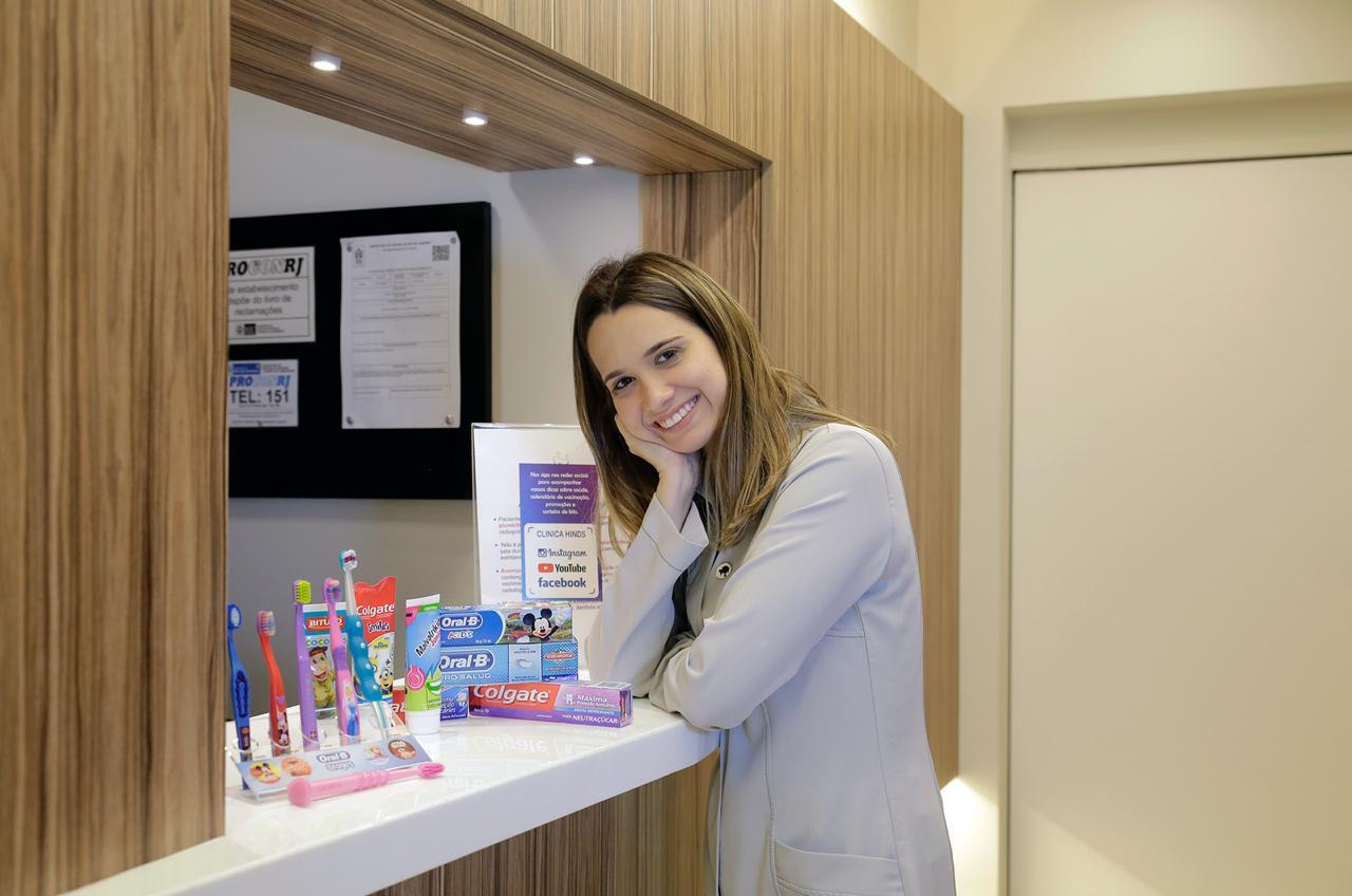 dentista ao lado de escovas e pastas de dente