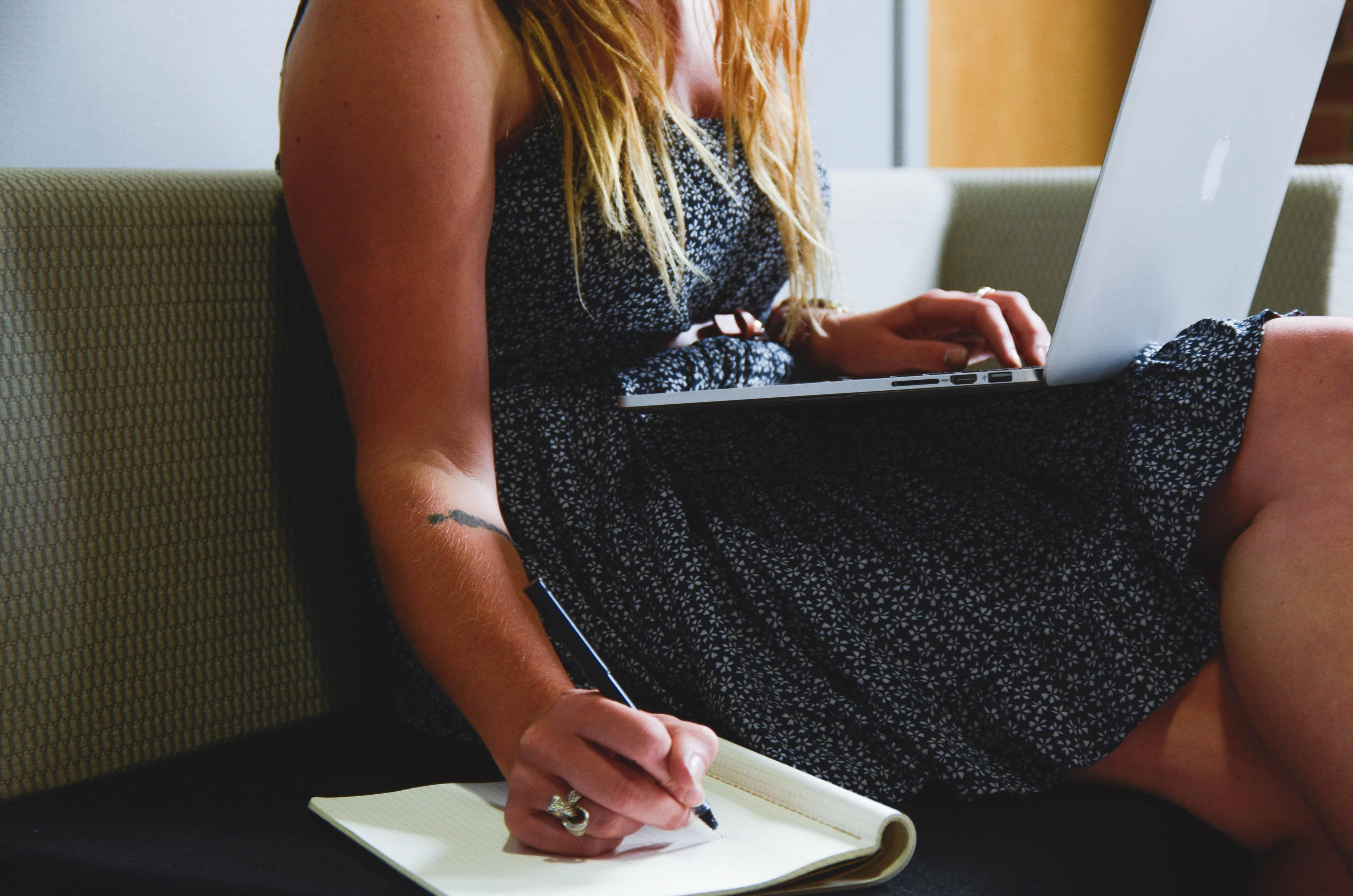 mulher sentada com um computador no colo escrevendo alguma coisa em um bloco de notas