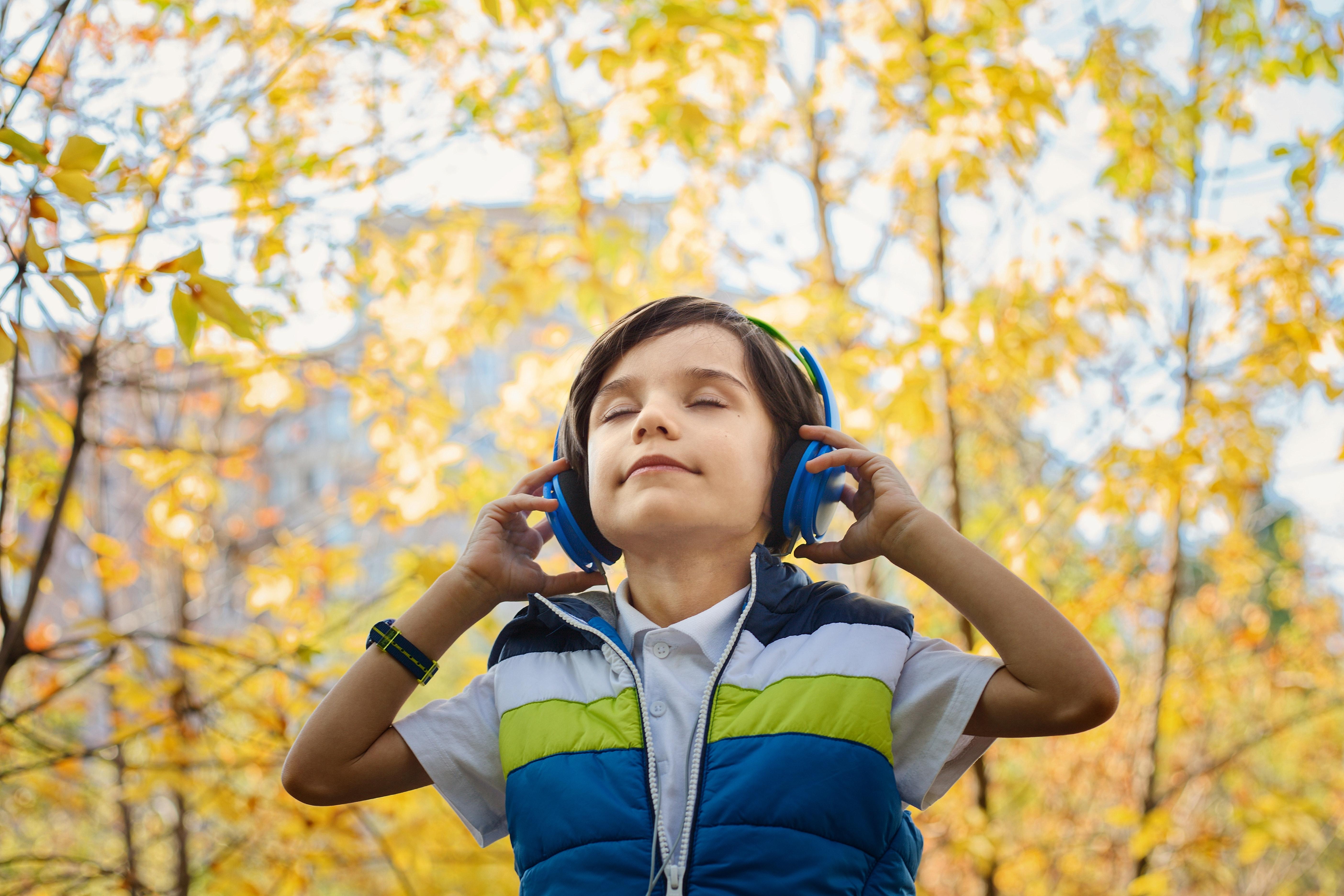 menino ouvindo música com um fone de ouvido em um lugar cheio de flores amarelas