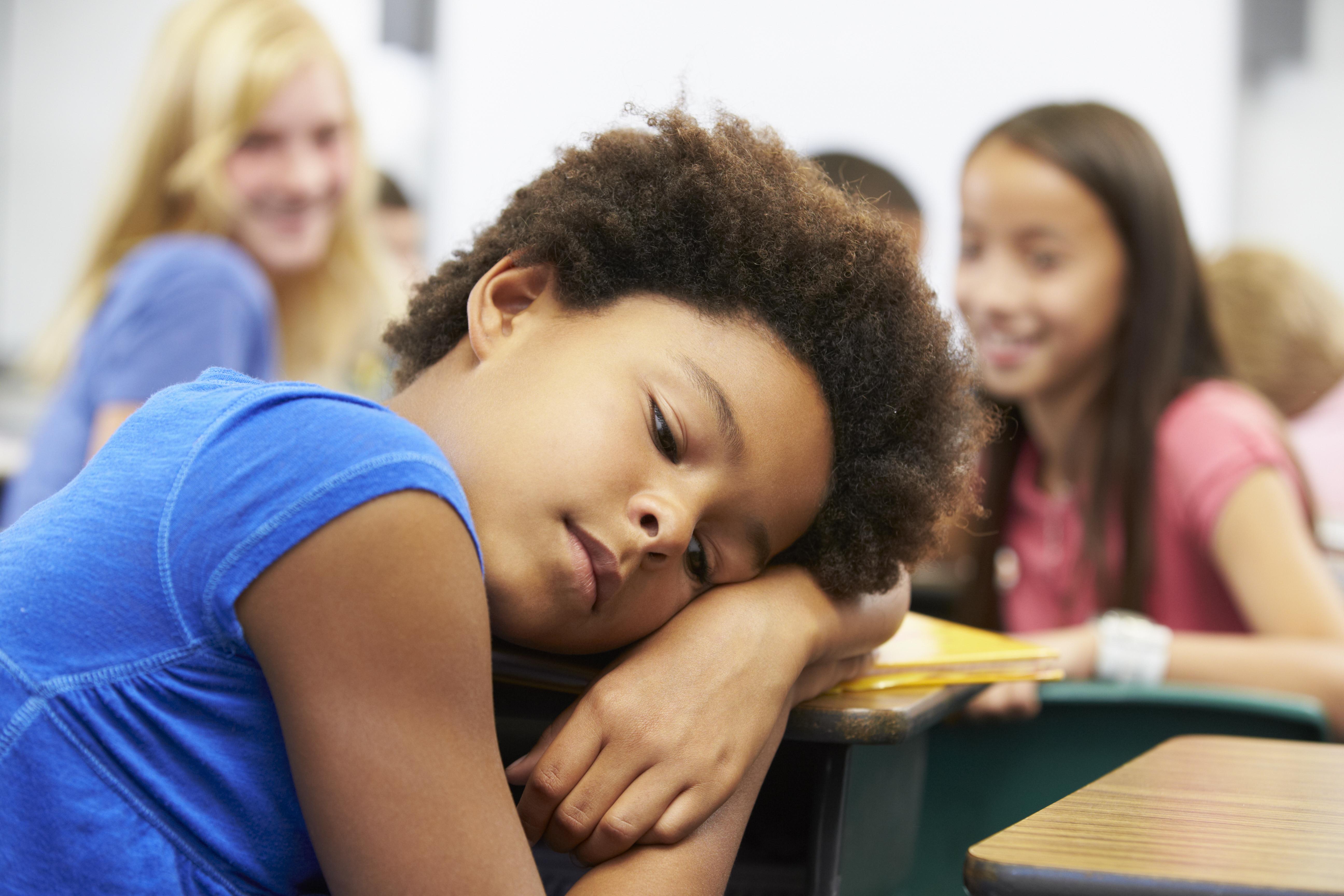 criança negra em primeiro plano com crianças rindo dela em segundo plano