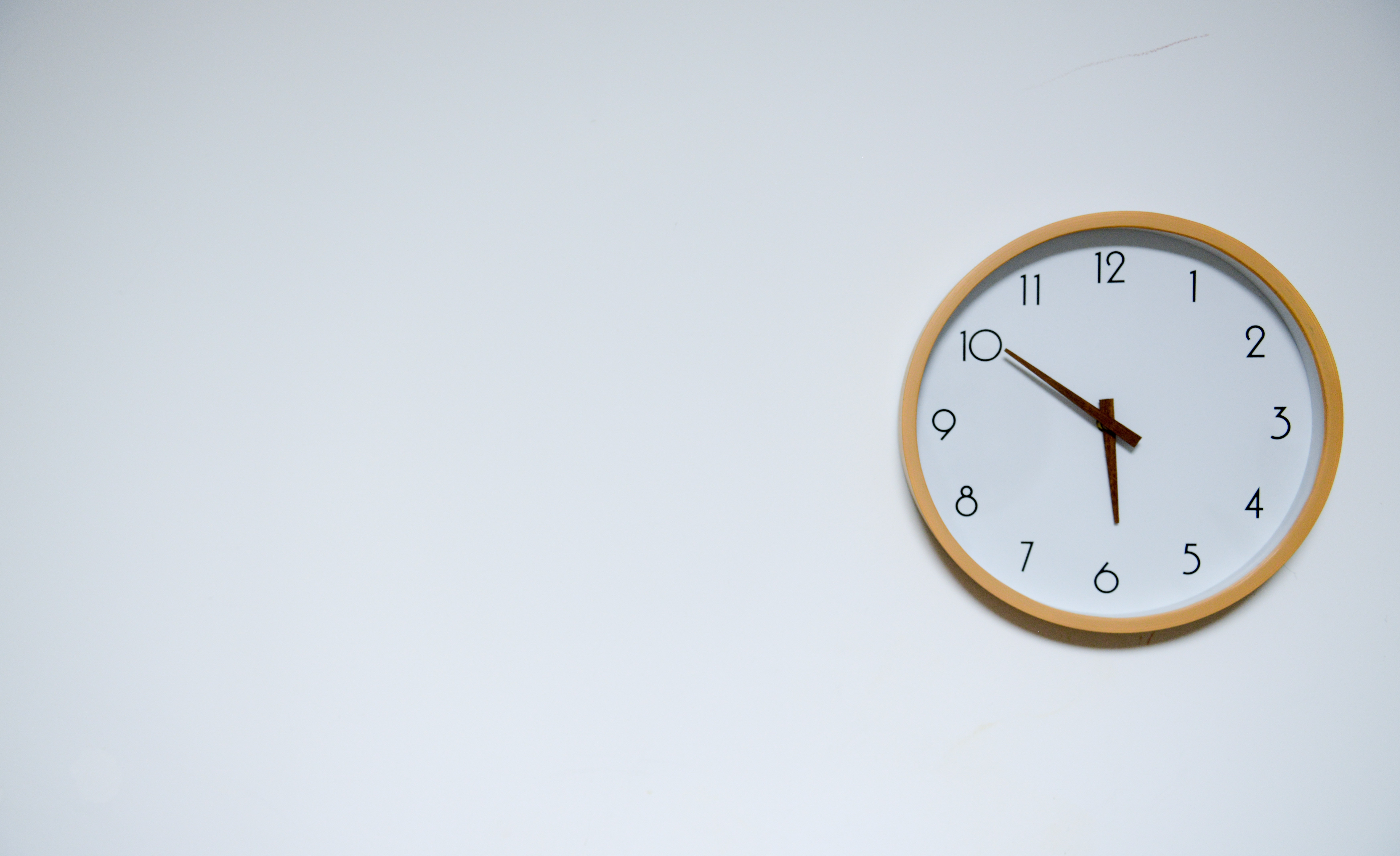 relógio marcando 5:50 pendurado em uma parede branca