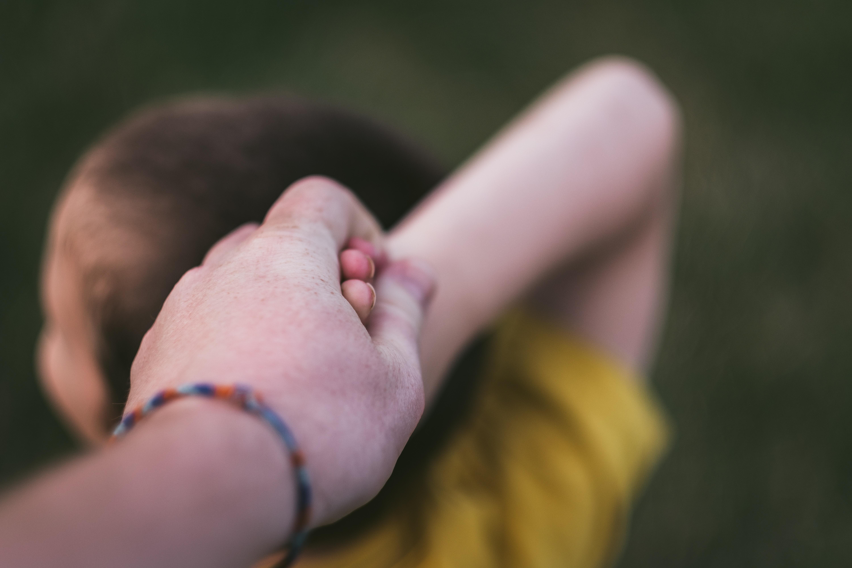 mãos dadas de um adulto com uma criança