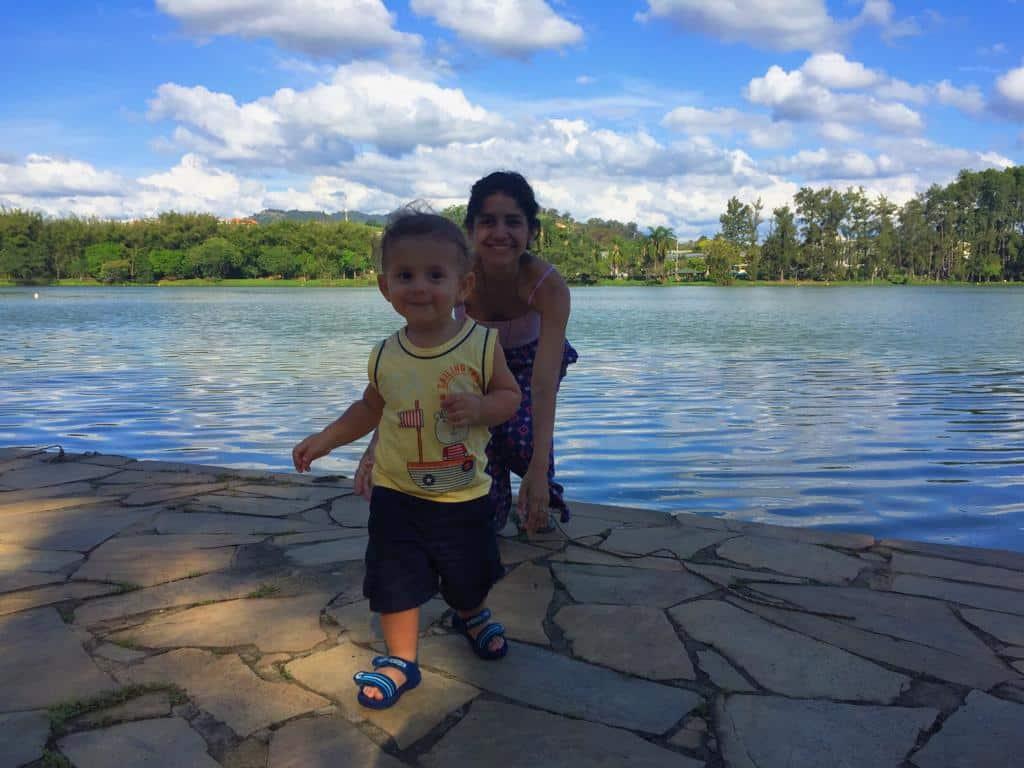 bebê correndo e uma mulher correndo atrás dele com um lago de fundo