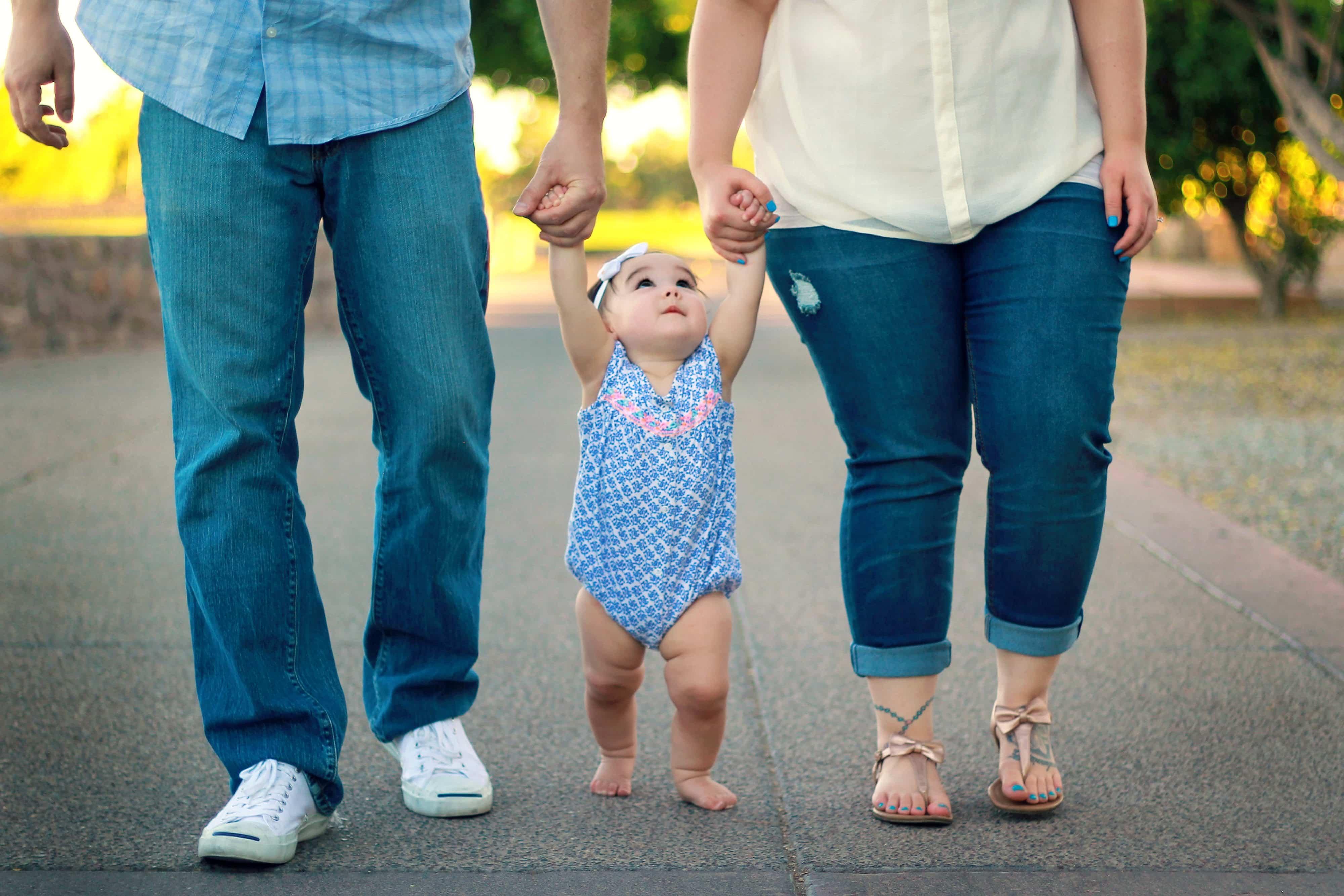 bebê entre duas pessoas sendo levando pela mão por um homem e uma mulher