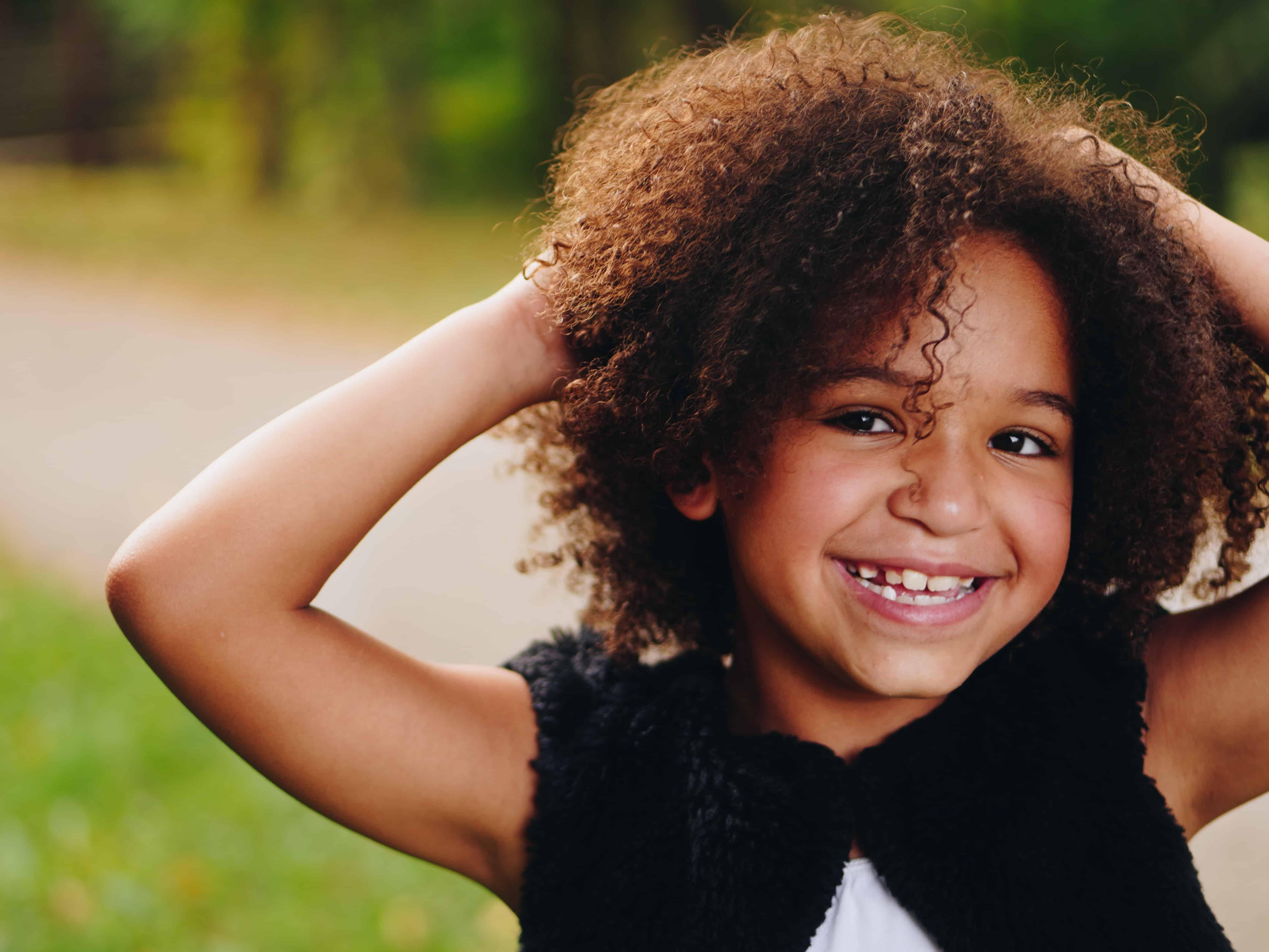criança negra com o cabelo enrolado sorrindo
