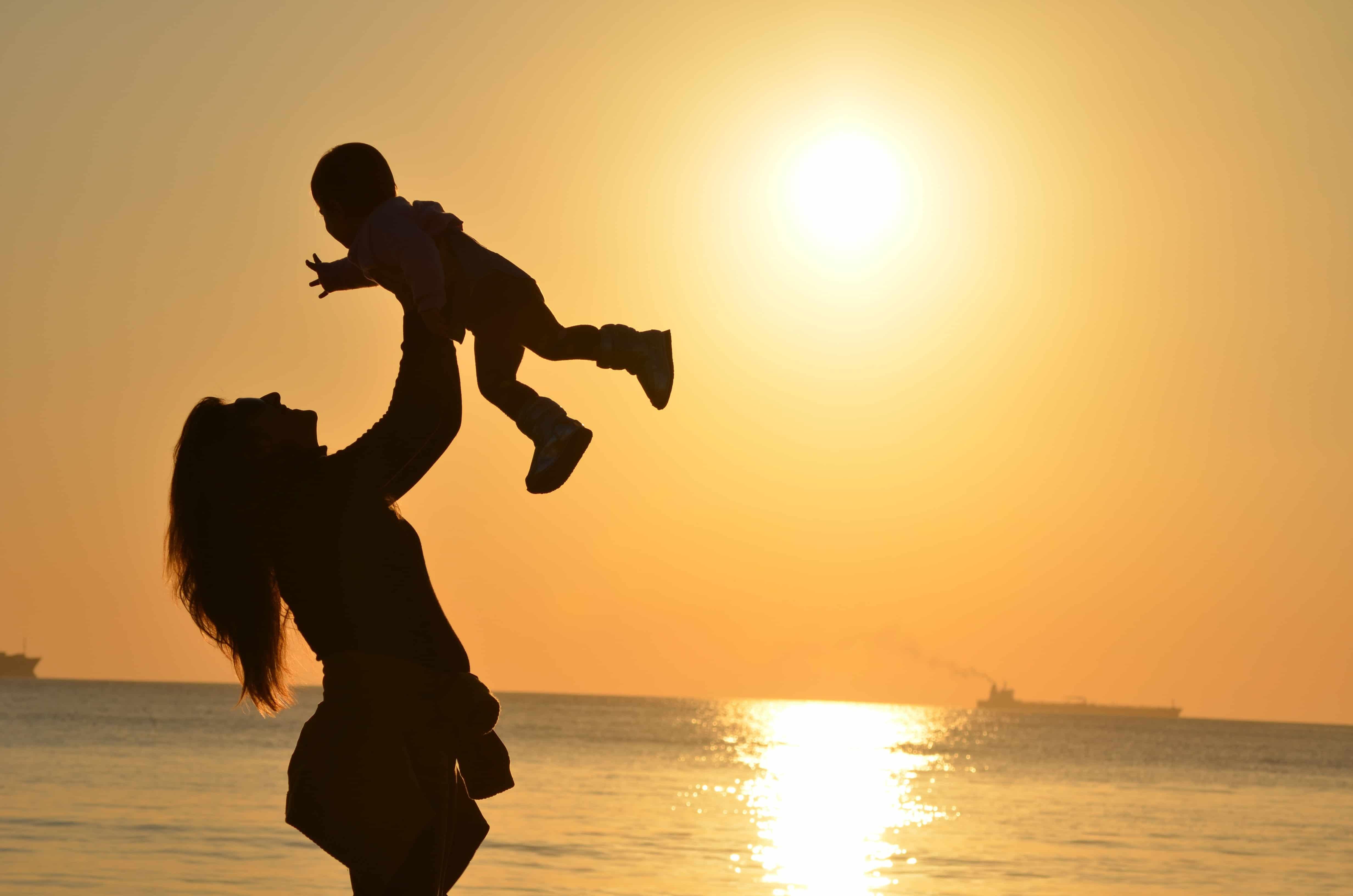 mulher levantando criança no por do sol