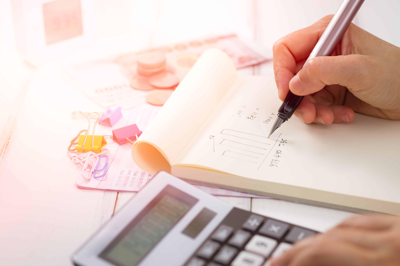 mão escrevendo em um caderno e uma calculadora ao lado