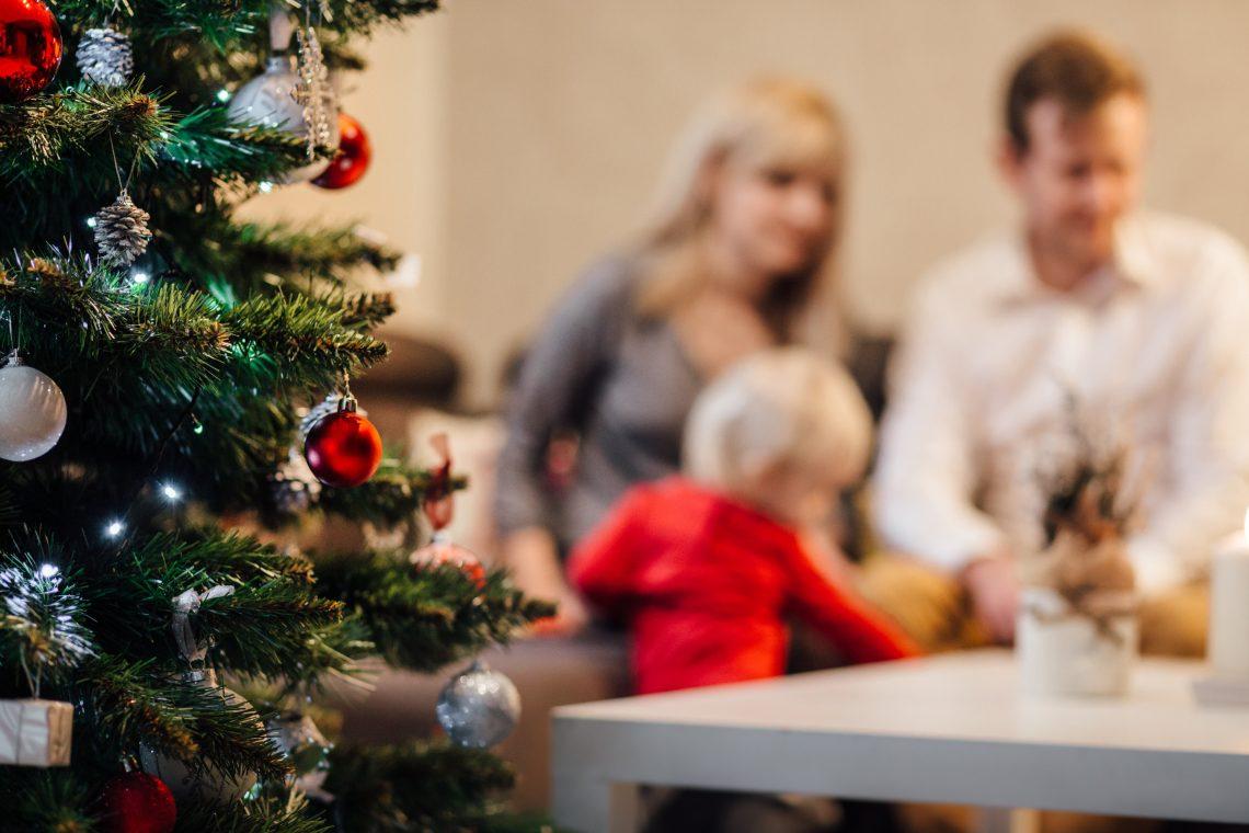 família com pai, mãe e criança sentados ao lado de uma arvores de natal