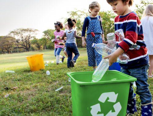 crianças colocando lixo dentro de cestos