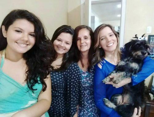 4 mulheres juntas sorrindo, uma delas segura o cachorro