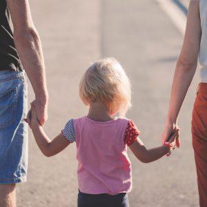 criança de mãos dadas com dois adultos