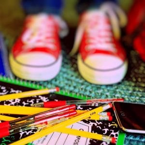 tênis vermelho pisando em lápis e livros
