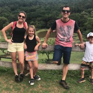 mulher, menina, homem e menino encostados em uma cerca