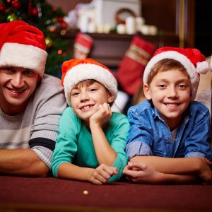 Pai, dois filhos e mãe, com gorro de natal