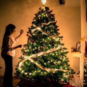 criança colocando uma bola de natal na árvore de Natal