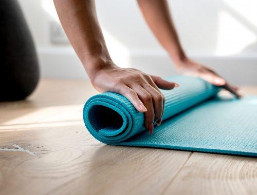 mão enrolando um tapete de yoga
