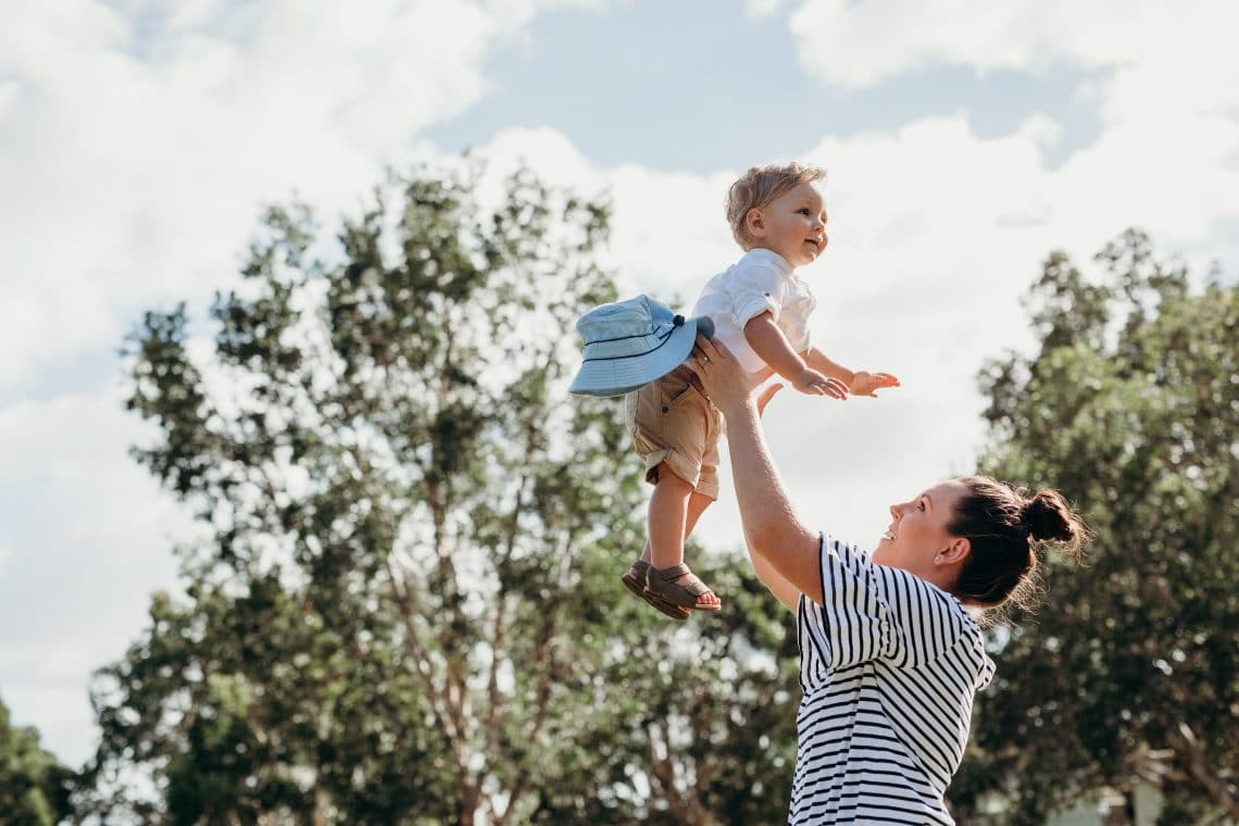 mãe levantando o filho para o céu