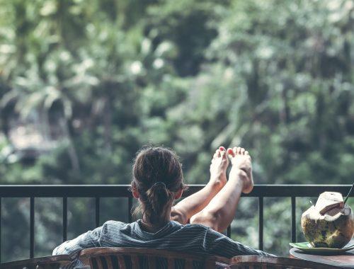 mulher sentando com o pé para cima em uma varanda olhando para uma área verde