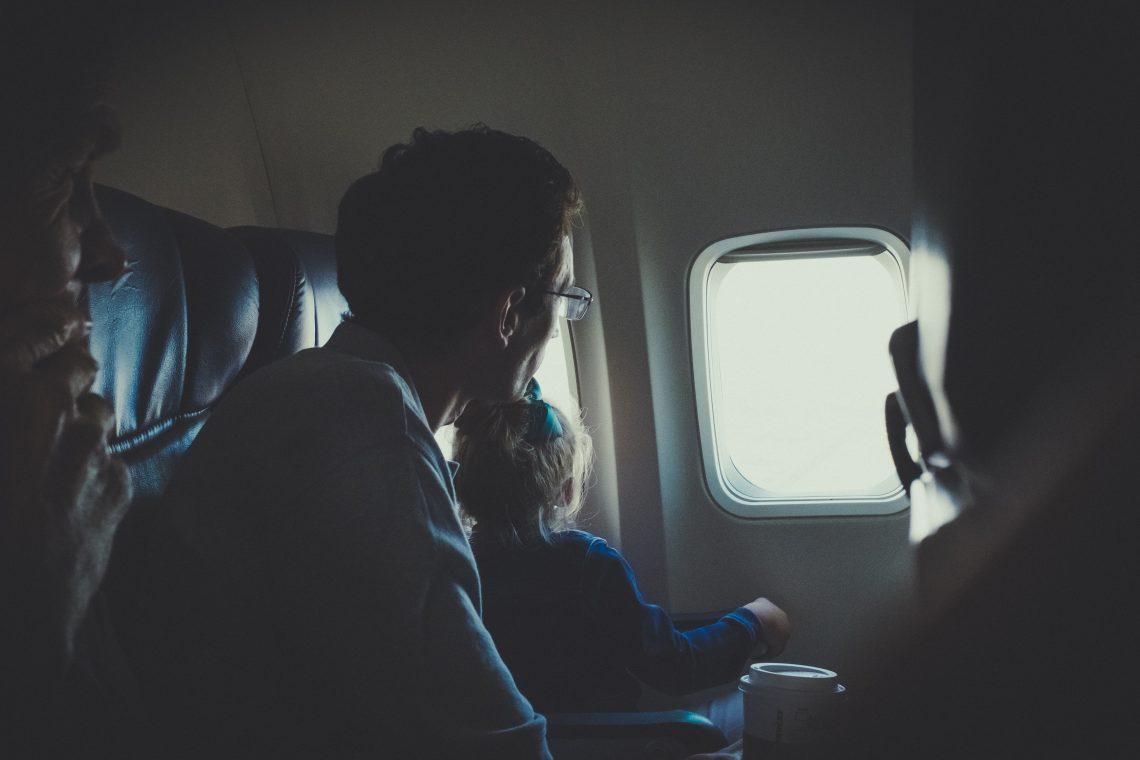 homem com uma criança pequena olhando a janela de um avião