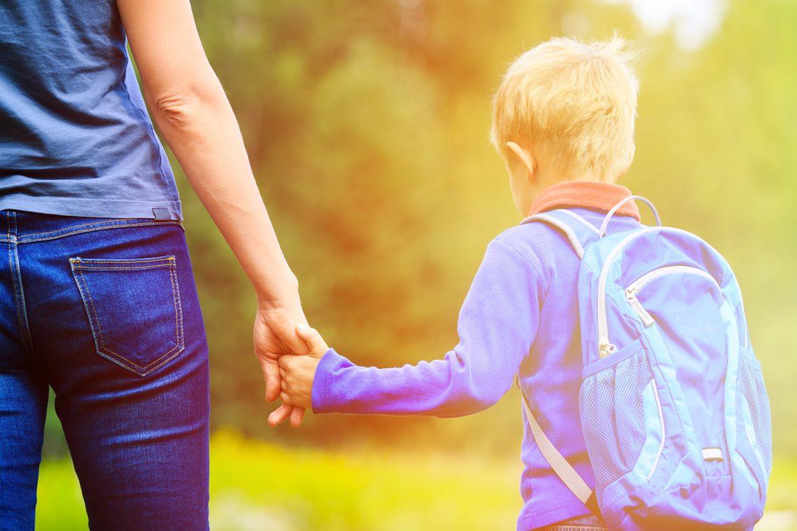 Mãe segurando a mão de uma criança com uma mochila nas costas