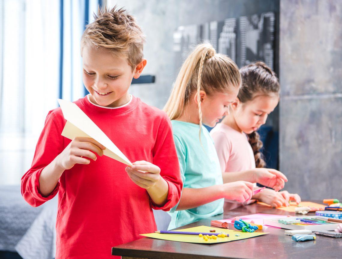 três crianças brincando com lapis e papel, tendo um menino com um avião de dobradura na mão