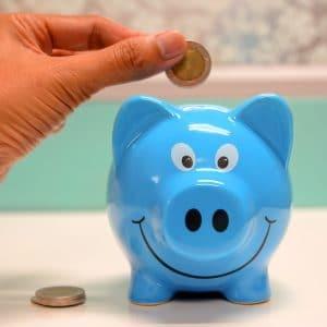 mão colocando dinheiro em um cofre de porco azul
