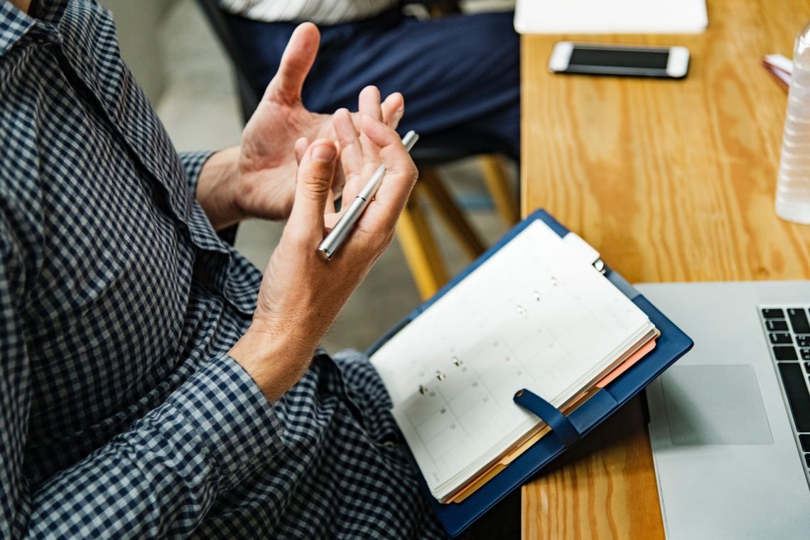 mãos de homem segurando uma caneta próxima a uma agenda