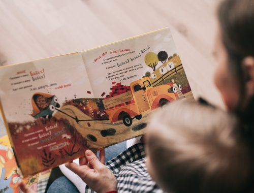 mãe com filho no colo lendo um livro