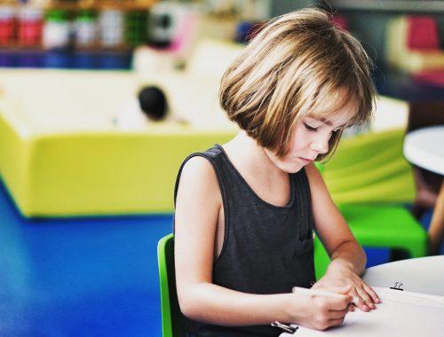 menina escrevendo em um ambiente escolar
