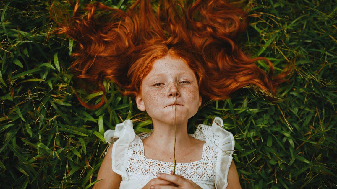 menina ruiva deitada na grama
