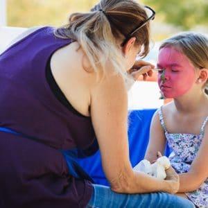 mãe pintando o rosto da filha de rosa