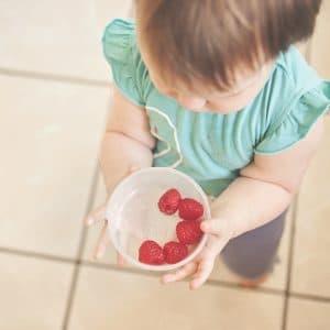 bebe com um pote de morango na mão