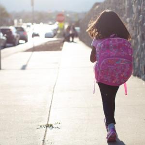 menina com mochila andando sozinha para escola