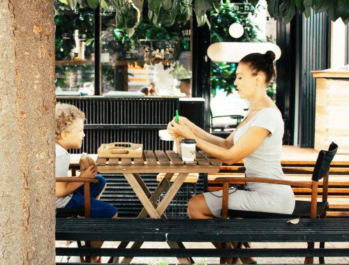 mulher ensinando o filho enquanto come